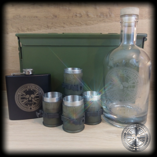 A picture of a green case with custom calibers engraved hip flask, glass bottle and mugs on top of a wooden surface
