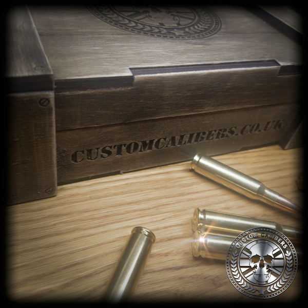 A picture of a wooden case with four bullets in front of it and the custom calibers logo at the bottom right