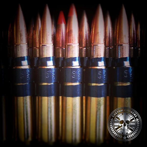 A picture of several bullets that are gold with red tips and the custom calibers logo at the bottom right