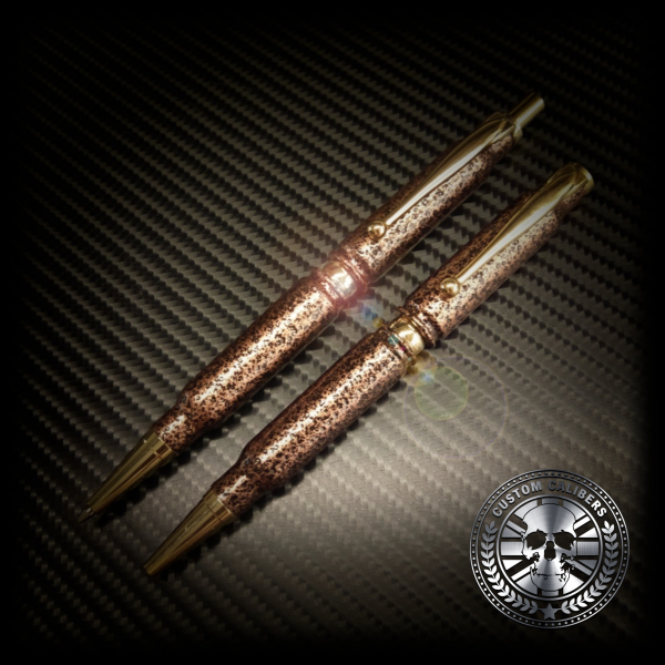 A picture of two bullet pens with the custom calibers logo at the bottom right