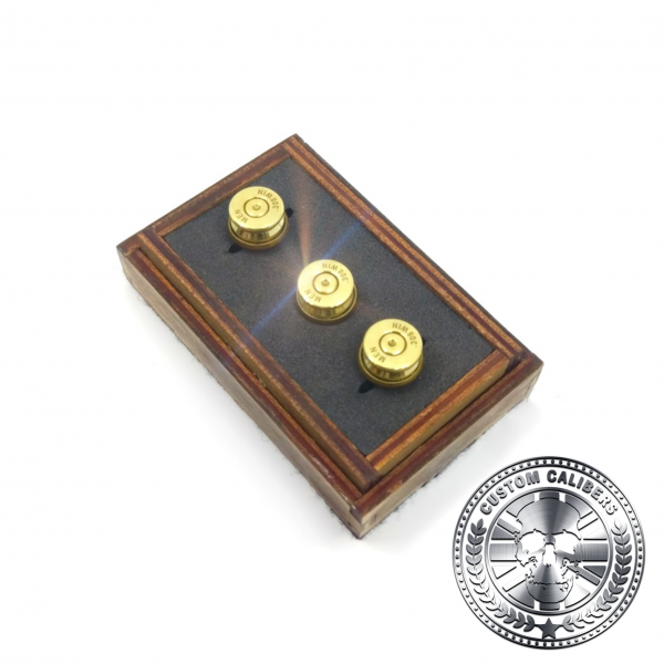 Yet another image of the same three golden cuff links in a wooden case with the custom calibers logo at the bottom right