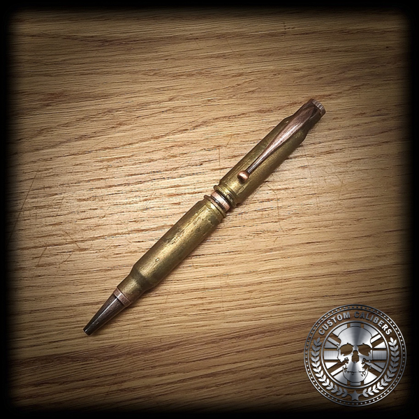 A golden bullet pen on a wooden surface with custom calibers logo at the bottom right