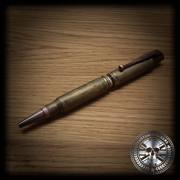 A picture of a golden bullet pen on a wooden surface with the custom calibers logo at the bottom right