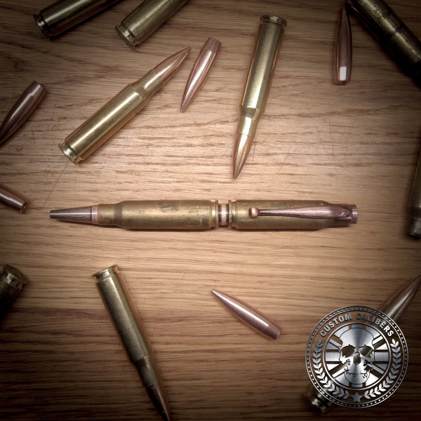 A truly incredible image of a golden bullet pen with many bullets surrounding it on a wooden table with the custom calibers logo at the bottom right