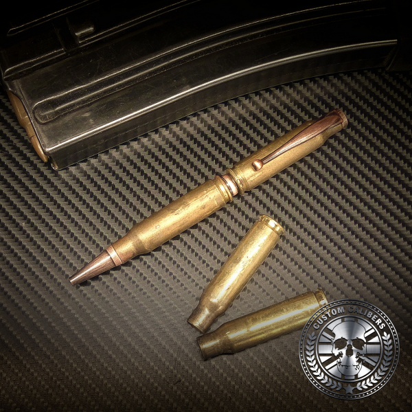 A golden bullet pen with two golden bullets and black gun magazine