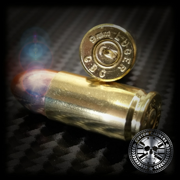 Another picture of two 9mm bullets on a smooth service with the custom calibers logo in the bottom right