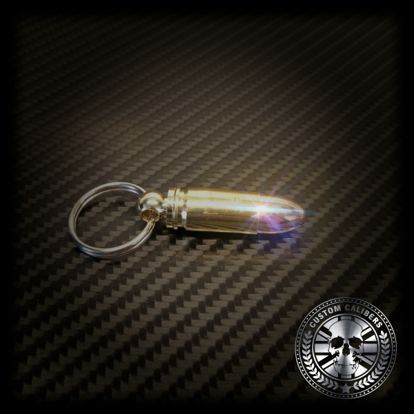 A professional picture of a 9mm bullet key ring on smooth surface with custom calibers logo at the bottom right