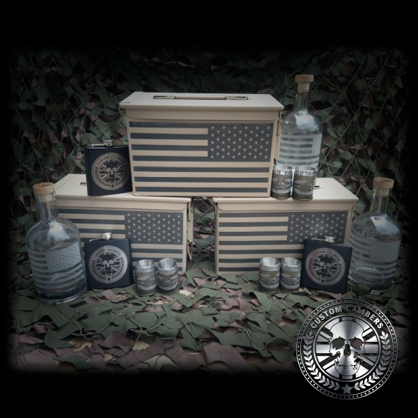 A photograph of three bottles with american flag as well as three cases with american flag plus three custom calibers hip flasks and six small steel mugs