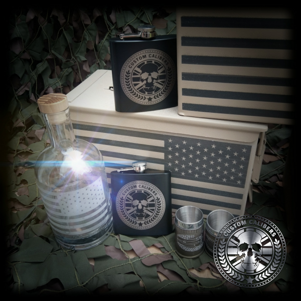 A picture of a bottle two custom calibers hip flasks and american flag cases with two steel mugs