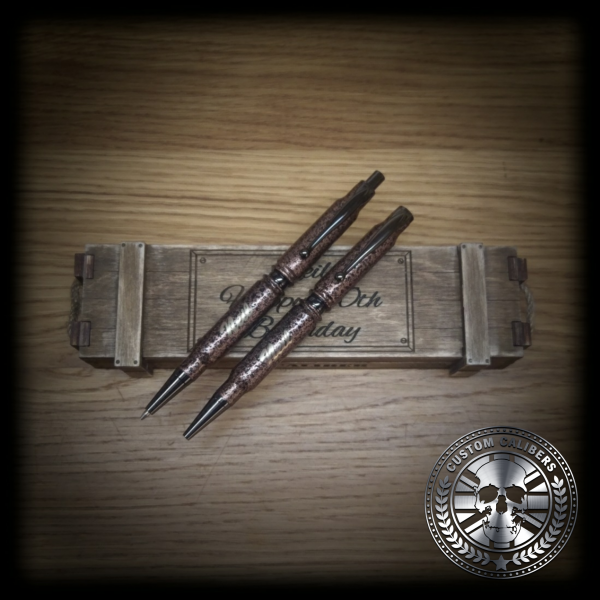 Another incredible image of two marble pens on a wooden case which is on a wooden background with the custom calibers logo
