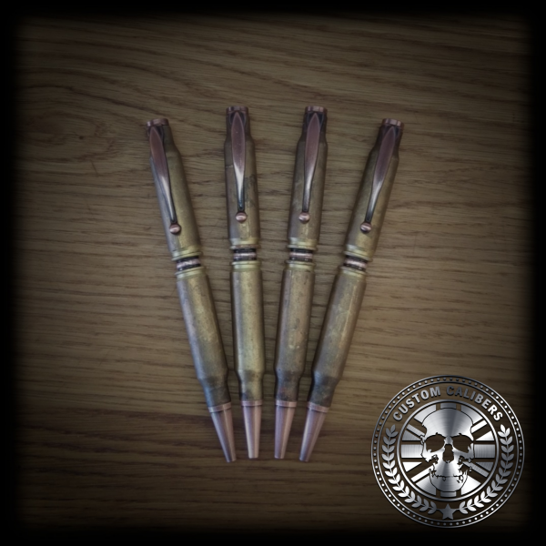 A picture of four pens on a wooden surface with custom calibers logo on the bottom right