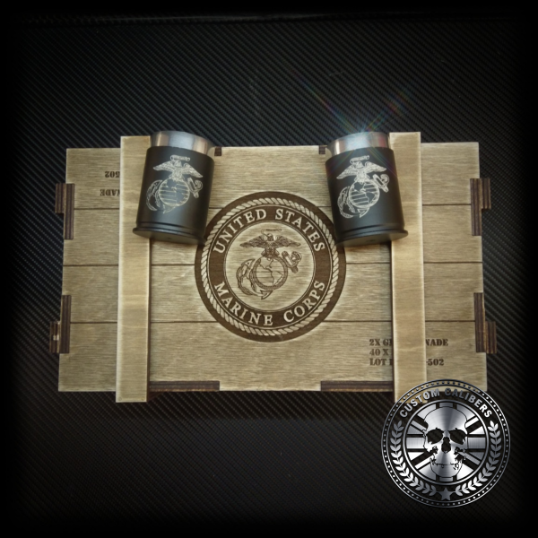 A photograph of a wooden case with two flasks on top with the custom calibers logo at the bottom right