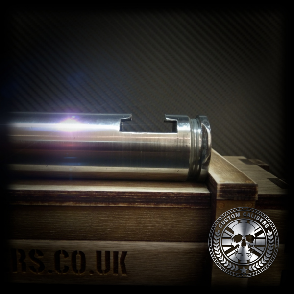 A professional picture of a silver artillery shell bottle opener on its side on a case with the custom calibers logo at the bottom right