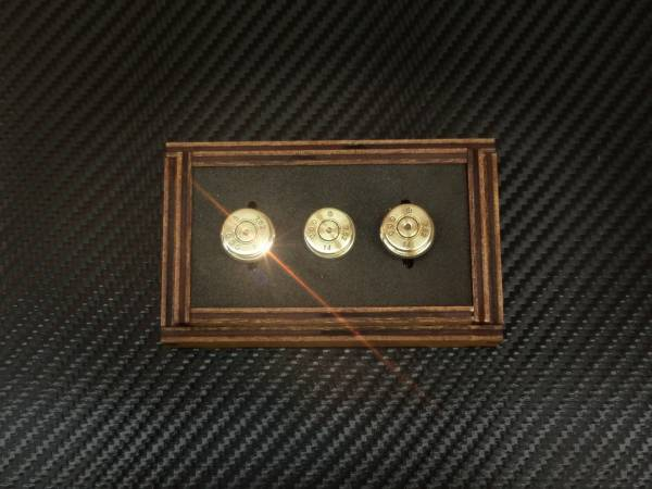A birds eye view picture of three golden bullet cuff links in a case