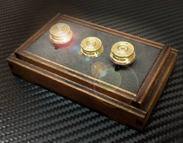 A professional image of three bullet cuff links in a case