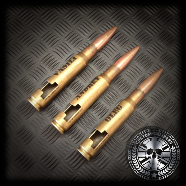 A mid range shot of three battle scarred .50 caliber bullet bottle openers with names engraved onto the front