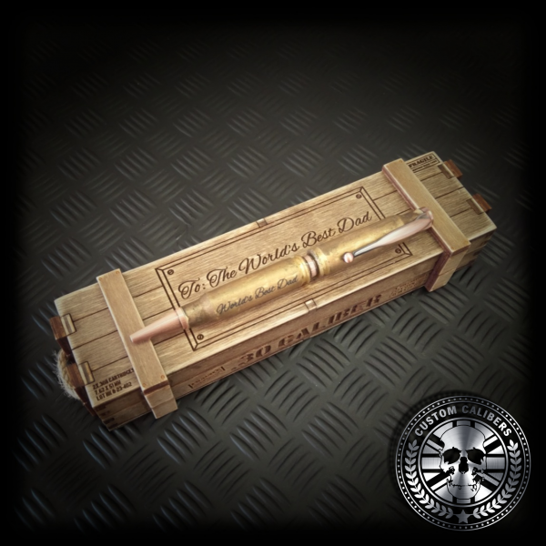 "angled shot of gold custom caliber bullet pen resting on top of glosed military gift crate, both the pen and the crate are inscribed with ""worlds best dad"""