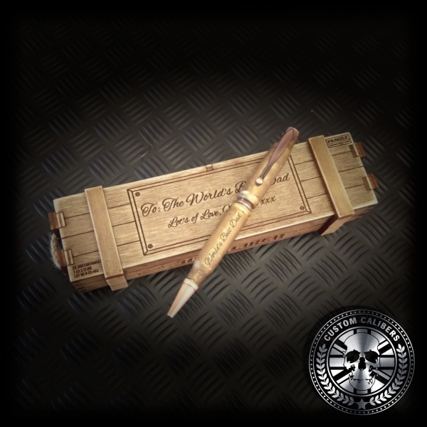 "gold custom caliber bullet pen with ""worlds best dad"" engraved on the cylinder, resting on an ammo gift crate with the same words inscribed on it"
