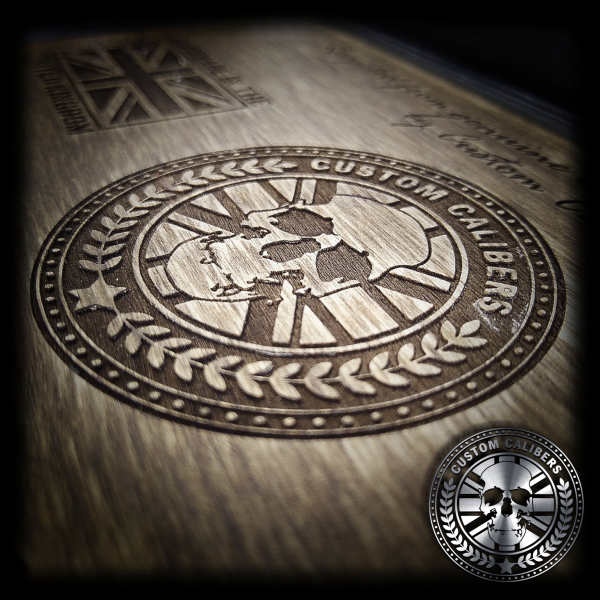An image of Custom Calibers engraved into wood