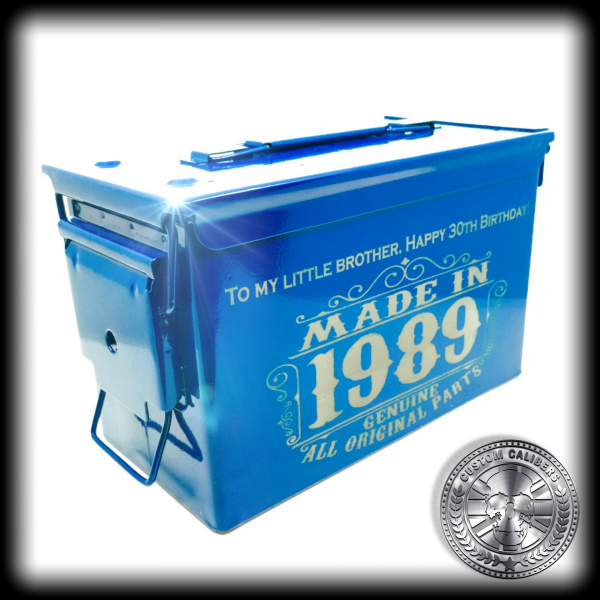 "a side shot of a powder coated ammo tin box in an airforce blue colour. it has been engraved with a custom design saying ""made in 1989"""