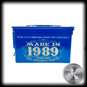 "a front shot of a powder coated ammo tin box in an airforce blue colour. it has been engraved with a custom design saying ""made in 1989"""