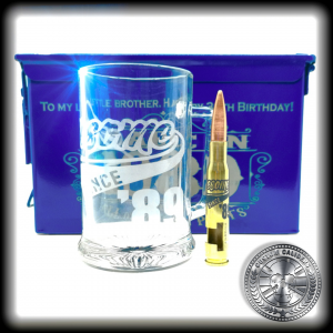 A mid range shot of a air force blue powder coated ammo tin gift set with matching engraved glass beer tankard and brass 50 cal bullet bottle opener
