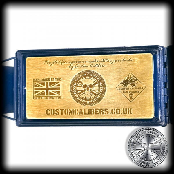 "A mid range shot of the inside of the ammo tin gift box lid showing an engraved wooden interior saying ""custom calibers.co.uk"" and the custom calibers company logo"