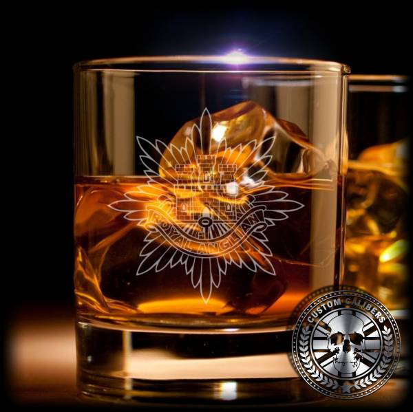 A glass of whiskey with ice and the royal anglian logo with the custom calibers logo on the bottom right