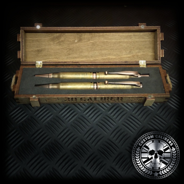 A mid range side facing shot of a matching set of battle-scarred bullet pen and bullet pencil laying inside the inside of the wooden presentation gift box