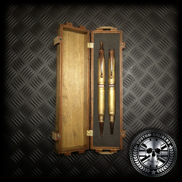 A mid range shot of a matching set of battle-scarred bullet pen and bullet pencil laying inside the inside of the wooden ammo crate gift box