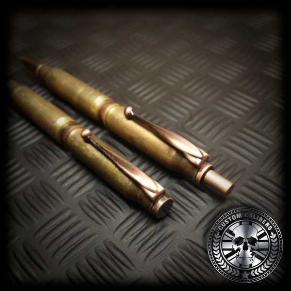 a close up shot of a matching set of battle-scarred bullet pen and bullet pencil laying flat showing the top of the pen and pencil
