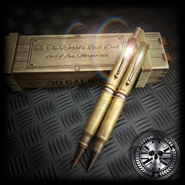 a mid range shot of a set of battle-scarred bullet pen and bullet pencil sitting on top of a handmade wooden ammo crate gift box with a custom engraving on the lid