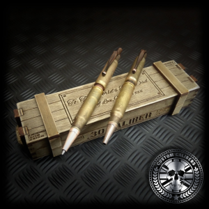 a close up shot of a matching set of bullet pen and bullet pencil sitting on top of a handmade wooden ammo crate gift box