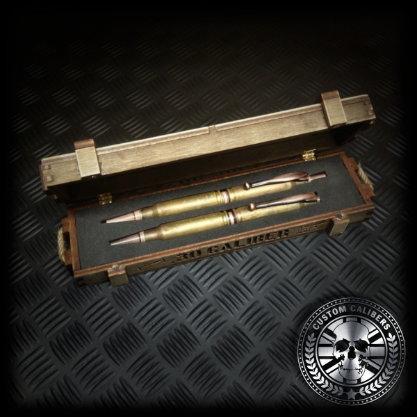 A mid range side shot of a matching battle-scarred bullet pen and bullet pencil made from real bullets displayed in a handmade wooden presentation ammo crate gift box
