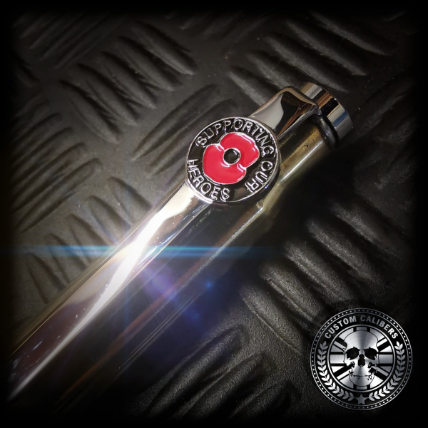 """A macro shot of the silver remembrance day poppy pen clip showing the red poppy saying """"supporting our heros"""" on the clip."""