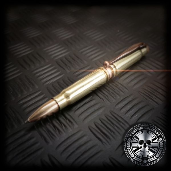 A close up shot of the polished brass AK-47 Bullet pen showing the real copper FMJ head used for the pen tip