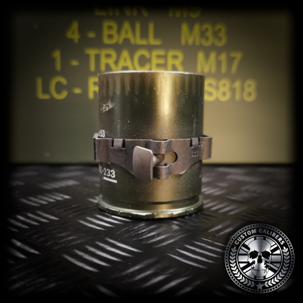A close up shot of the upcycled 40mm grenade drinking shot glass showing the linkage around the outside of the casing