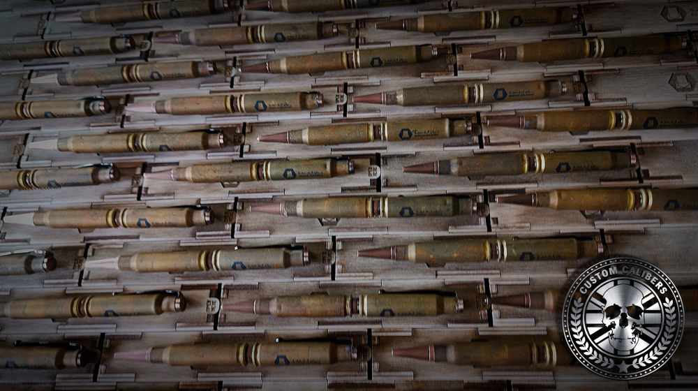 Another image of a lot of shells and bullets with the custom calibers logo at the bottom right