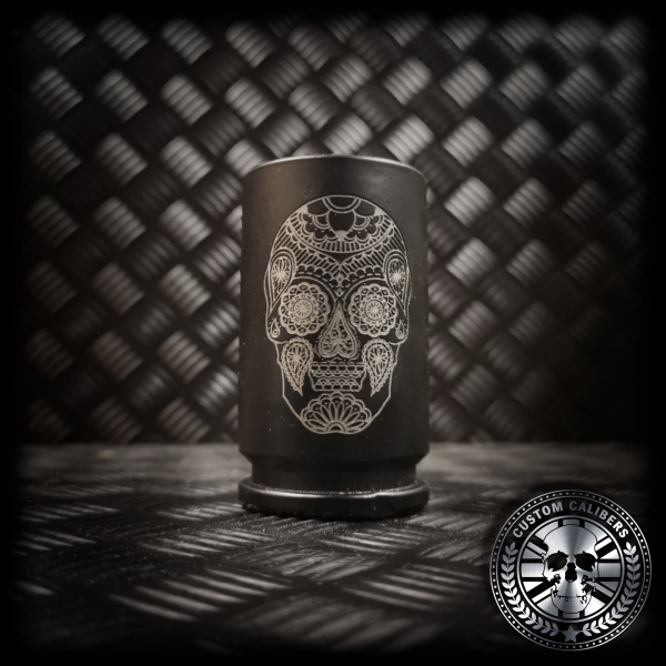 a matt black 30mm A10 Warthog casing cut and turned into an awesome shot glass engraved with a detailed Candy skull design