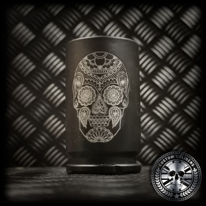 A close up of a matt black 30mm A10 shot glass showing a custom candy skull engraving