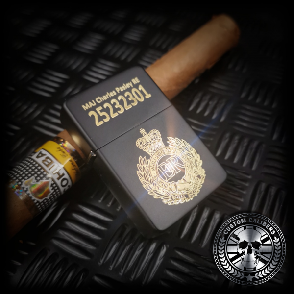 A matt black lighter engraved with the royal engineers crest resting on a cuban cigar
