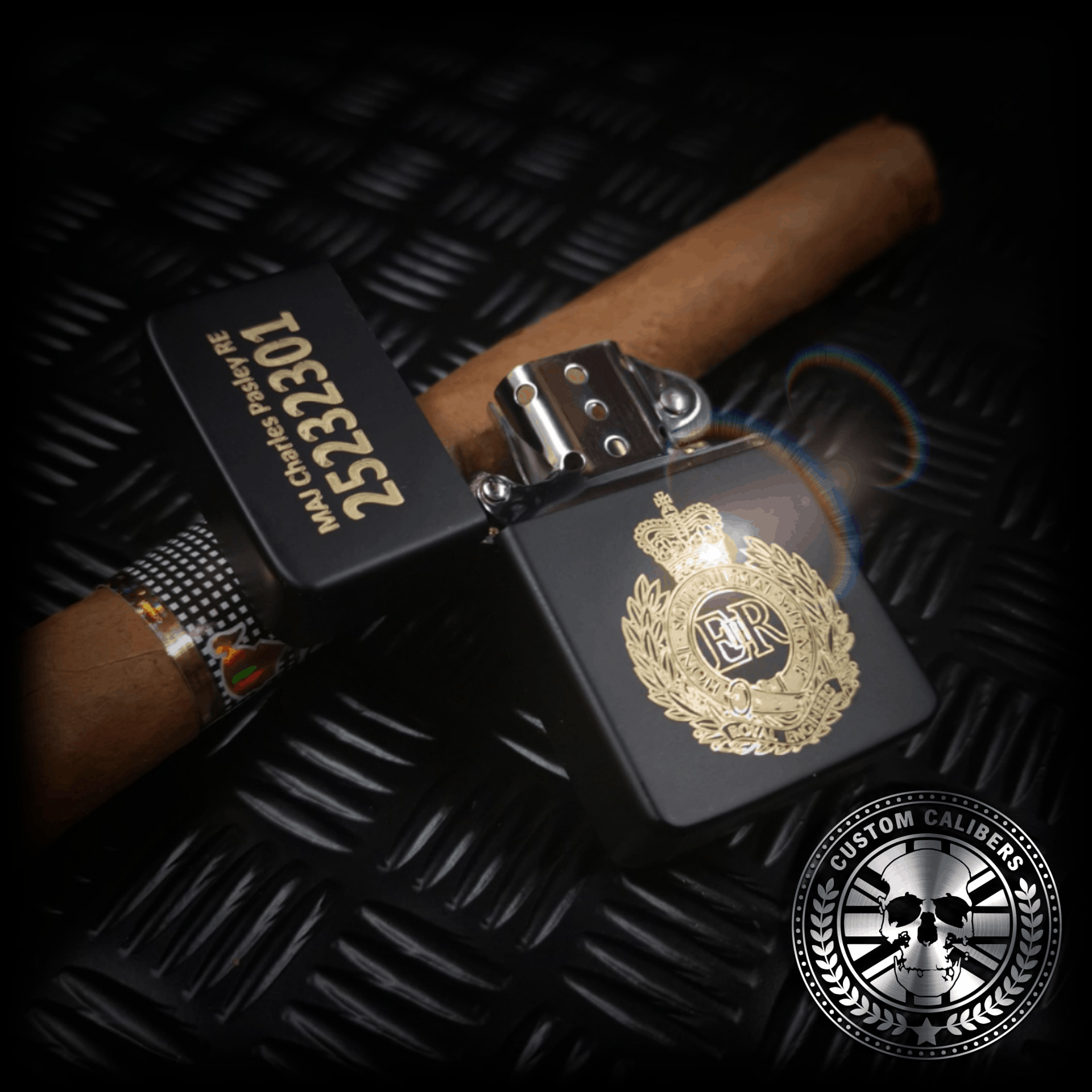 A matt black lighter with the lid open engraved with the royal engineers crest resting on a cuban cigar