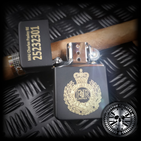 A close up of A matt black lighter with the lid open engraved with the royal engineers crest resting on a cuban cigar