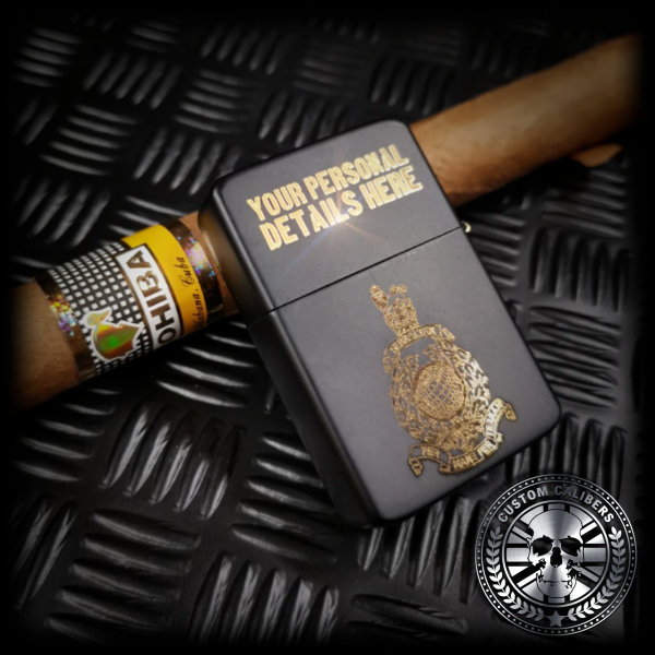 A matt black lighter with the lid open engraved with the royal marines crest resting on a cuban cigar