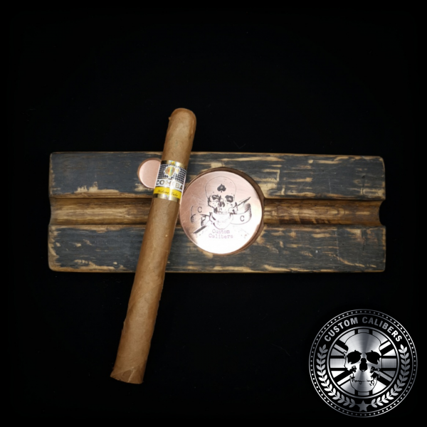 A cigar ashtray handmade from a whiskey stave barrel with a large Cuban Cohiba cigar resting on top