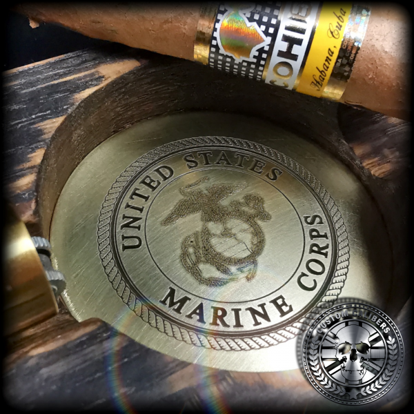 a close up shot of the engraved brass cigar ash tray insert with the USMC crest