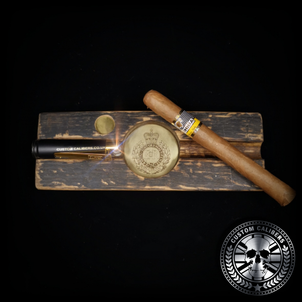 A perfect shot of a cigar ashtray handmade from a whiskey stave barrel with a large Cuban Cohiba cigar and bullet lighter resting on top