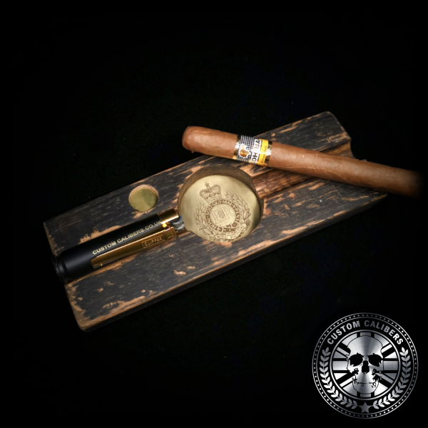 An awesome photo of a cigar ashtray handmade from a whiskey stave barrel with a large Cuban Cohiba cigar and bullet lighter resting on top. the ash tray is engraved with the royal engineers crest in the middle