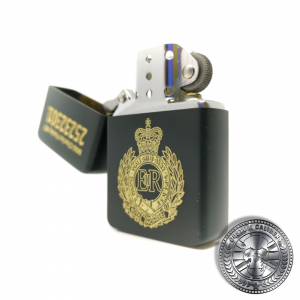 A close up shot of a matt black solid brass flip top lighter engraved with the royal engineers crest on the front with a name and military service number on the lid which has been opened to show the inside of the lighter