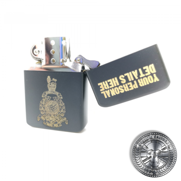 A close up shot of a matt black solid brass flip top lighter engraved with the royal marines crest on the front with a name and military service number on the lid which has been opened to show the inside of the lighter